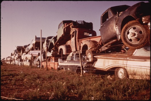 Junked Automobiles Are Piled Three Deep Along Fence